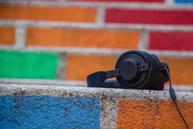 Headphones on a coloured brick wall